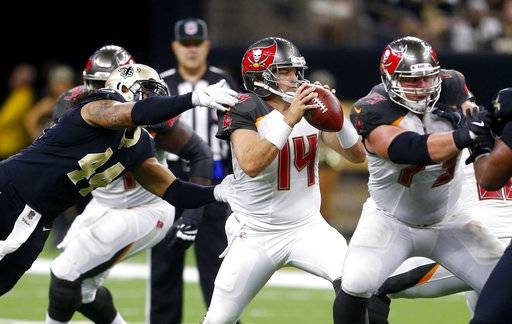 FILE - In this Nov. 5, 2017, file photo, Tampa Bay Buccaneers quarterback Ryan Fitzpatrick (14) scrambles under pressure from New Orleans Saints outside linebacker Hau'oli Kikaha (44) during the second half of an NFL football game in New Orleans. Fitzpatrick and New York Jets' Josh McCown are survivors, aging quarterbacks who keep getting opportunities to prove their worth to NFL teams. The two teams play this week.