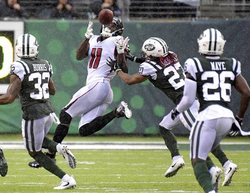 FILE - In this Oct. 29, 2017, file photo, Atlanta Falcons wide receiver Julio Jones (11) catches a pass for a 53-yard gain as New York Jets cornerbacks Juston Burris (32) and Darryl Roberts (27) and free safety Marcus Maye (26) look on during the second half of an NFL football game in East Rutherford, N.J. When the Cowboys and the Falcons meet Sunday in a critical NFC match, the winner will be in solid position for a run toward the playoffs.