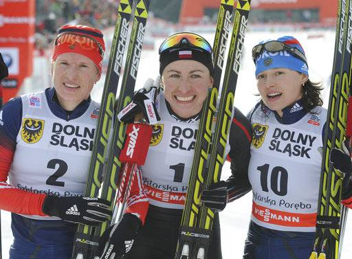 FILE - In this Sunday, Jan. 19, 2014 file photo, second placed Russia's Yulia Tchekaleva, left, winner Poland's Justyna Kowalczyk, center, and third placed Russia's Yulia Ivanova pose for photographers after the women's Cross Country skiing 10km Mass Start Classic World Cup event in Szklarska Poreba, Poland. Four more Russian cross-country skiers have been found guilty of doping at the 2014 Sochi Olympics, it was announced on Thursday, Nov. 9, 2017. The Russian Cross-Country Ski Federation says the four have been disqualified by the International Olympic Committee and banned from all future Olympics. The other three skiers found guilty are Alexei Petukhov, Yulia Ivanova and Evgenia Shapovalova. Vylegzhanin won three silver medals in Sochi, but none of the others won a medal.
