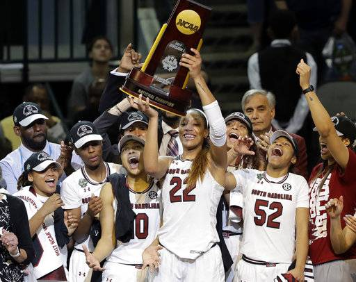 FILE - In this April 2, 2017, file photo, South Carolina forward A'ja Wilson (22) holds up the trophy as she celebrates with teammates after their 67-55 win over Mississippi State in the final of the NCAA women's Final Four college basketball tournament in Dallas. South Carolina won 67-55. After a thrilling Final Four in April that ended with the Gamecocks winning their first national championship, women's college basketball is ready to get started Friday