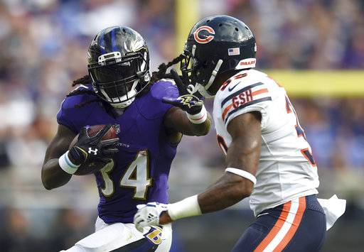 FILE - In this Oct. 15, 2017, file photo, Baltimore Ravens running back Alex Collins, left, rushes against Chicago Bears free safety Eddie Jackson during the second half of an NFL football game in Baltimore. Provided additional playing time after an injury to starter Terrance West, Collins ranks 10th in the NFL with 521 yards rushing and is averaging 5.6 yards per carry