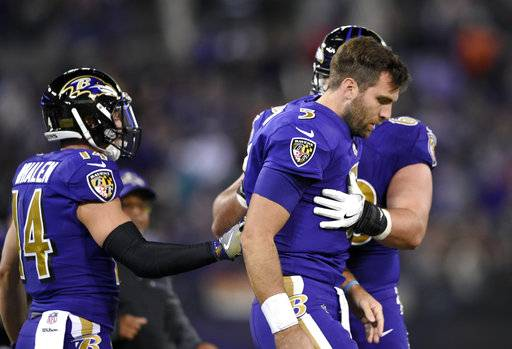FILE - In this Oct. 26, 2017, file photo, Baltimore Ravens quarterback Joe Flacco, right, is assisted off the field after being tackled by Miami Dolphins middle linebacker Kiko Alonso during the first half of an NFL football game in Baltimore. Following an unusual summer in which he skipped most of training game and all four preseason games, Flacco has not come close to approaching the form he's displayed in his previous nine NFL seasons. He has thrown 10 interceptions compared to eight touchdown passes and is averaging an NFL-low 5.33 yards per attempt.