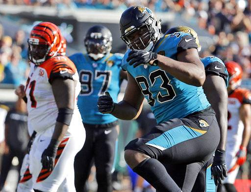 FILE - In this Sunday, Nov. 5, 2017, file photo, Jacksonville Jaguars defensive lineman Calais Campbell (93) celebrates a big play against the Cincinnati Bengals during the second half of an NFL football game  in Jacksonville, Fla. Two statistics often sway the voting for the defensive player of the year award: sacks and interceptions. Certainly the quarterback traps Jacksonville has gotten, led by Calais Campbell, have impressed the voters.