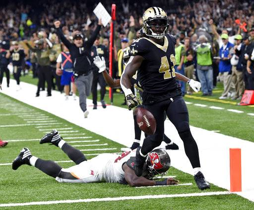FILE - In this Sunday, Nov. 5, 2017, file photo, New Orleans Saints running back Alvin Kamara (41) carries for a touchdown past a diving Tampa Bay Buccaneers defensive tackle Clinton McDonald in the first half of an NFL football game in New Orleans. Texans quarterback Deshaun Watson probably had surpassed Kareem Hunt, Leonard Fournette and Alvin Kamara when he went down before Week 9 with a torn ACL. That seems to put the race for this award in the cleats of those running backs.