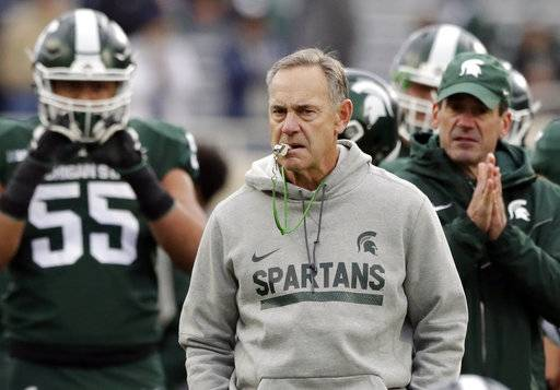 FILE - In this Saturday, Nov. 4, 2017, file photo, Michigan State head coach Mark Dantonio watches warmups before an NCAA college football game against Penn State in East Lansing, Mich. When the Big Ten Conference expanded to 14 teams by adding Rutgers and Maryland it realigned to simple East and West divisions. That put Ohio State, Penn State, Michigan State and Michigan together. With Nebraska struggling to find its way back to consistent top-20 status, it's left a concentration of power in the East that will be difficult to balance.