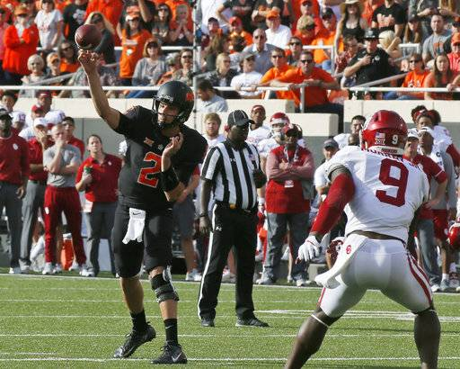 Oklahoma State quarterback Mason Rudolph (2) passes in front of Oklahoma linebacker Kenneth Murray (9) in the first half of an NCAA college football game in Stillwater, Okla., Saturday, Nov. 4, 2017. (AP Photo/Sue Ogrocki)