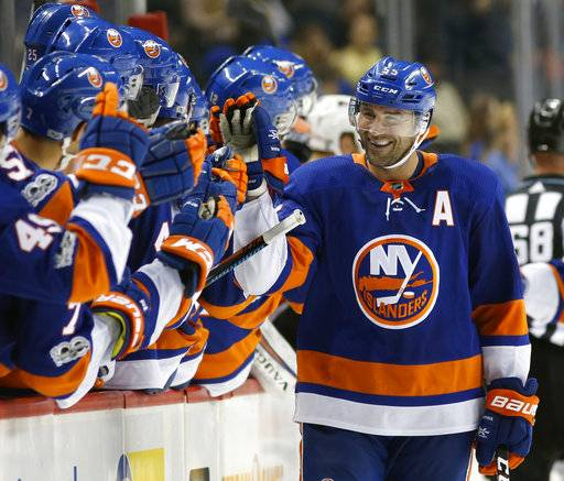 FILE - In this Sept. 20, 2017, file photo, teammates congratulate New York Islanders' Johnny Boychuk (55) after he scored a goal during the third period of a preseason NHL hockey game against the Philadelphia Flyers, in New York. New NHL faceoff violation enforcement has pressed more defensemen in to taking draws this season. Like position players pitching, defensemen taking faceoffs after not practicing is a rare challenge.