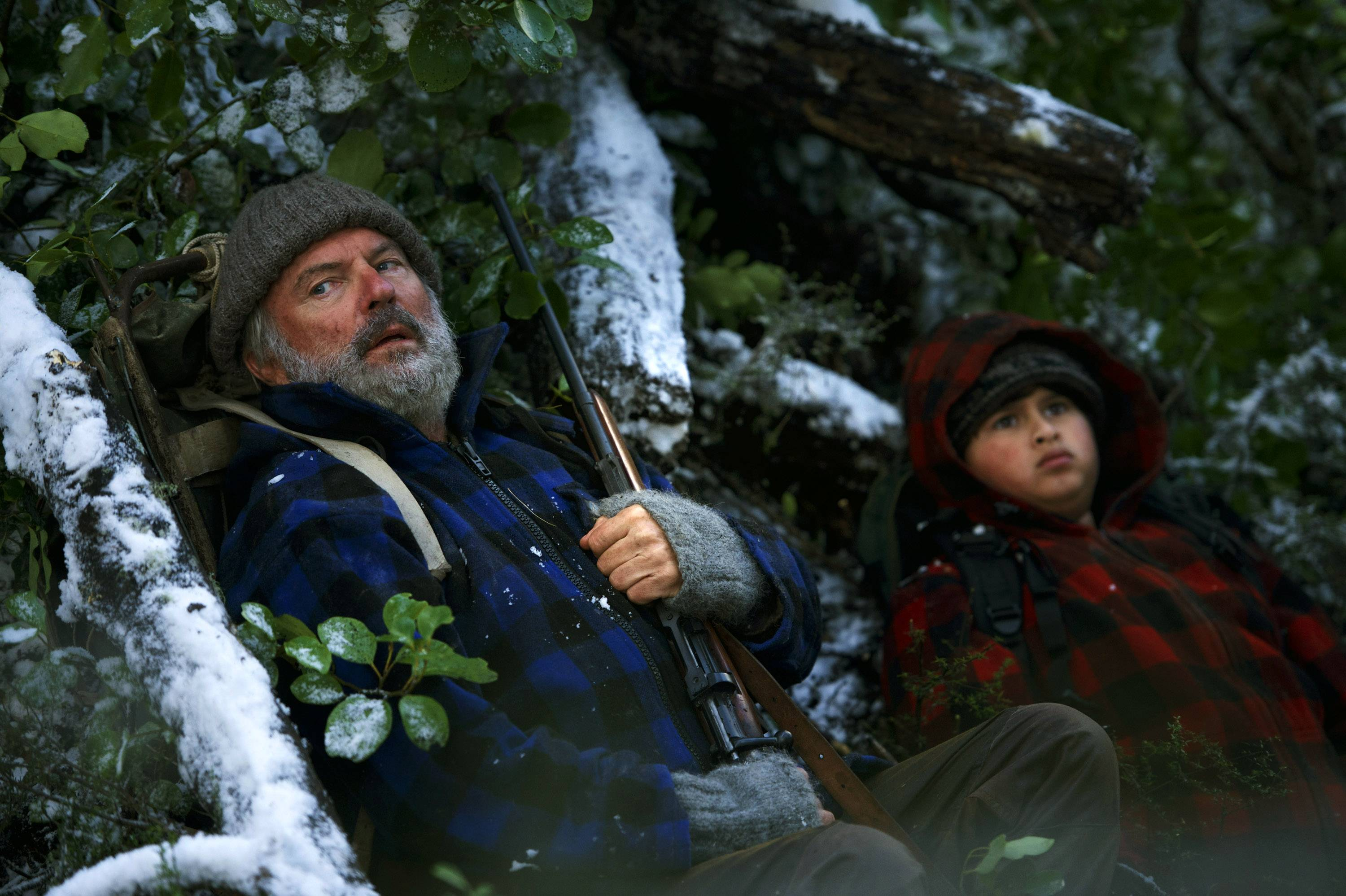 "A bristly hunter (Sam Neill) and his foster son (Julian Dennison) brave the New Zealand bush to escape authorities in ""Hunt for the Wilderpeople."""