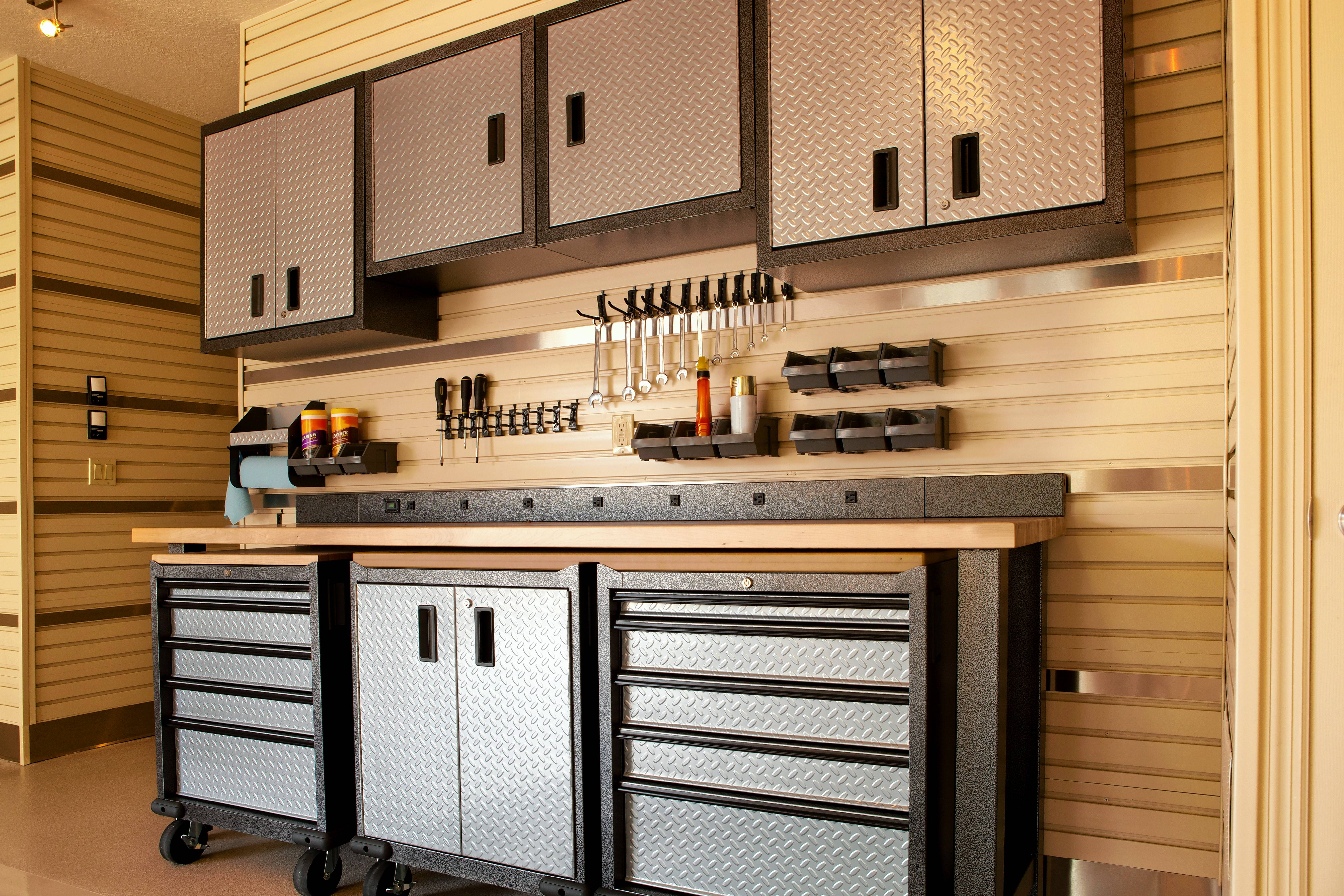 Garage workspaces with cabinets and a countertop make it easy to store tools and keep organized.