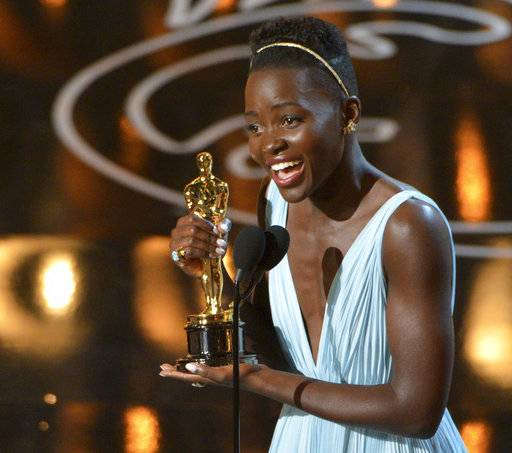 "FILE - In this Sunday, March 2, 2014 file photo, Lupita Nyong'o accepts the award for best actress in a supporting role for ""12 Years a Slave"" during the Oscars at the Dolby Theatre in Los Angeles. British magazine Grazia U.K. on Friday Nov. 10, 2017, has apologized to Lupita Nyong'o after the actress accused it of altering her hair on its front cover ""to fit a more Eurocentric notion"" of beauty. (Photo by John Shearer/Invision/AP, File)"