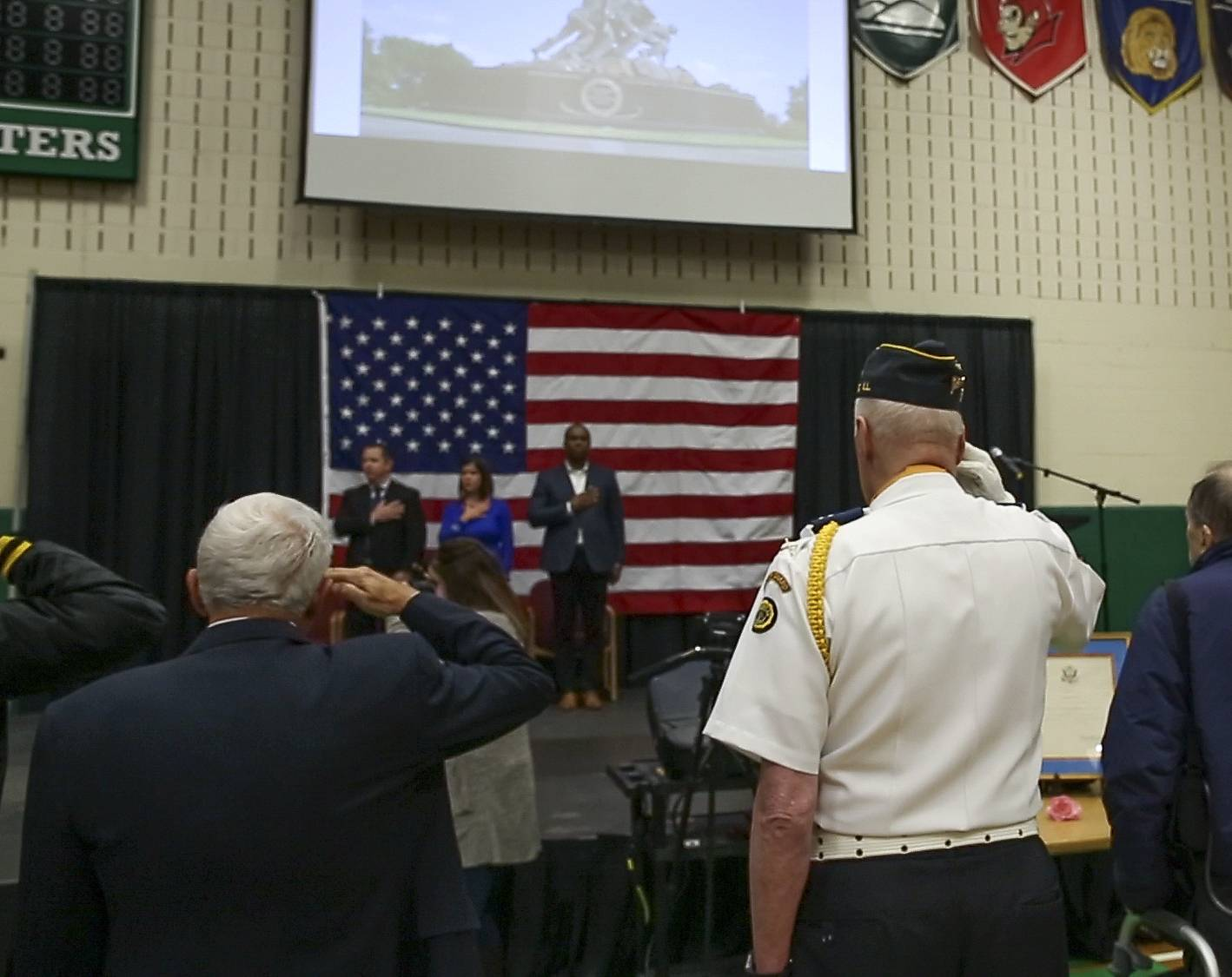 Veterans salute during the national anthem at the ceremony Friday at York High School.