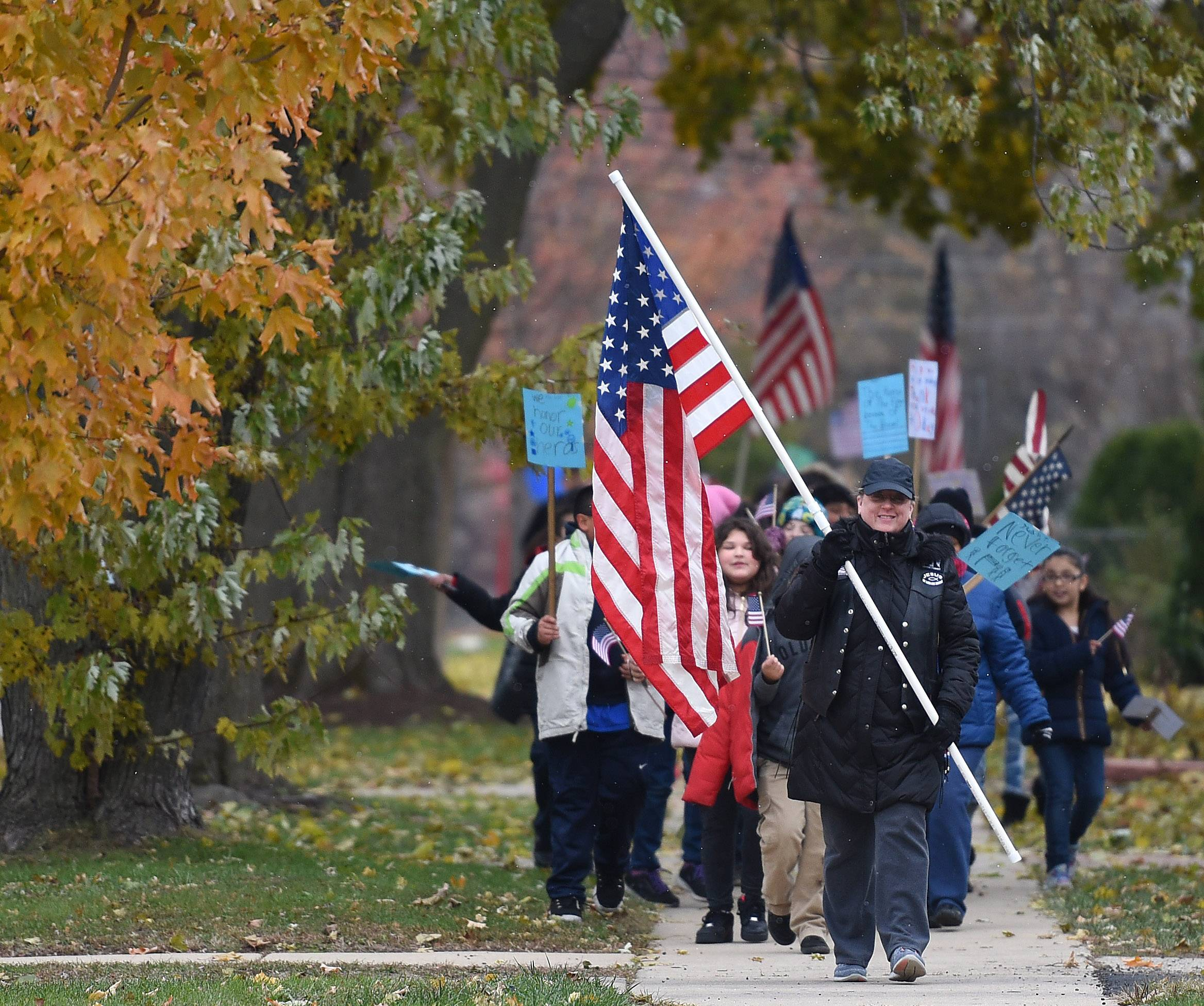 Fourth-grade teacher Ani Smith leads students from Ronald D. O'Neal Elementary School in Elgin as walk to the Veterans Memorial Park Friday to commemorate Veterans Day.
