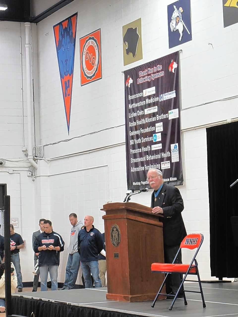 "Harvey Barnum, a Medal of Honor recipient who spent 27 years serving in the Marines, promotes the value of hard work in a ""cruel world"" during a Veterans Day assembly Friday at Naperville North."