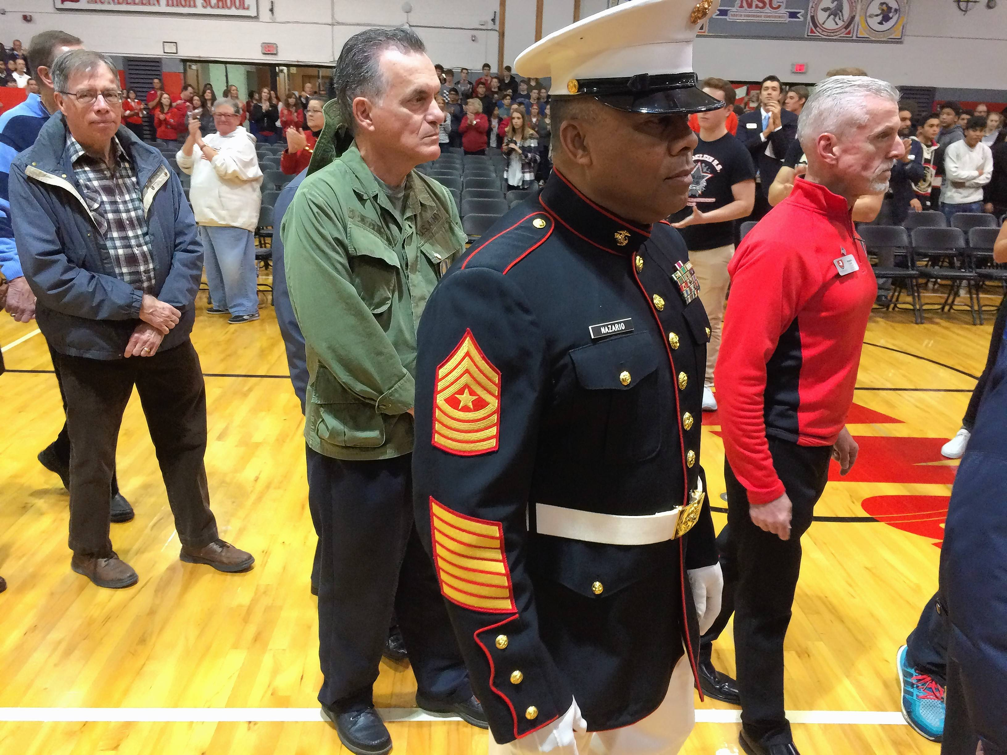 Retired U.S. Marine Sgt. Maj. Jose Nazario, in uniform, enters the Mundelein High School gymnasium with other military veterans for a Friday ceremony honoring veterans.