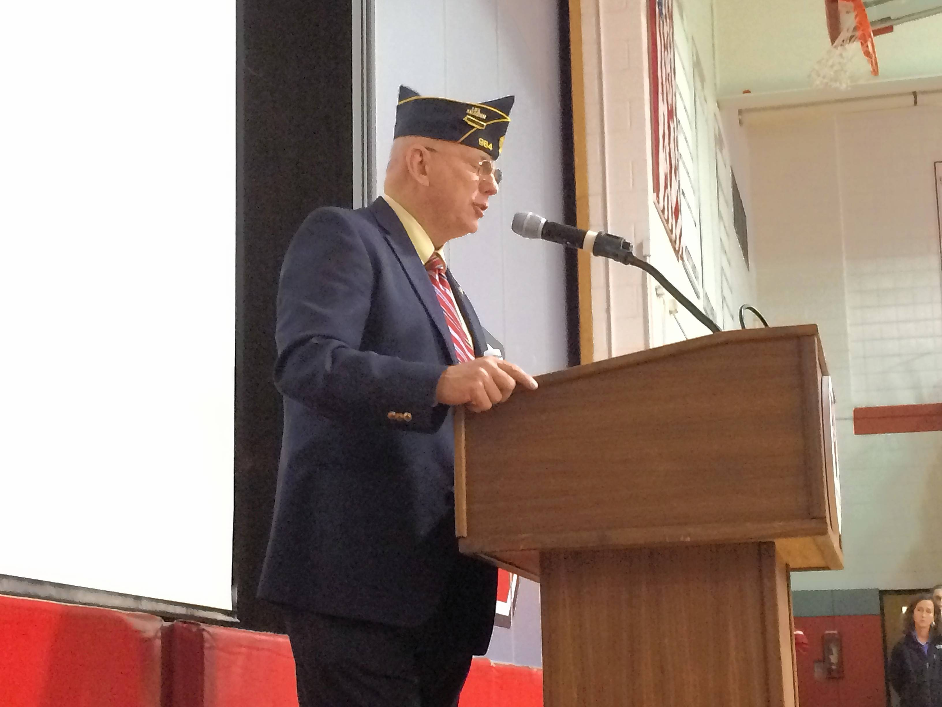 Retired U.S Army Col. Michael Peck talks about military history Friday during a ceremony honoring veterans at Mundelein High School.
