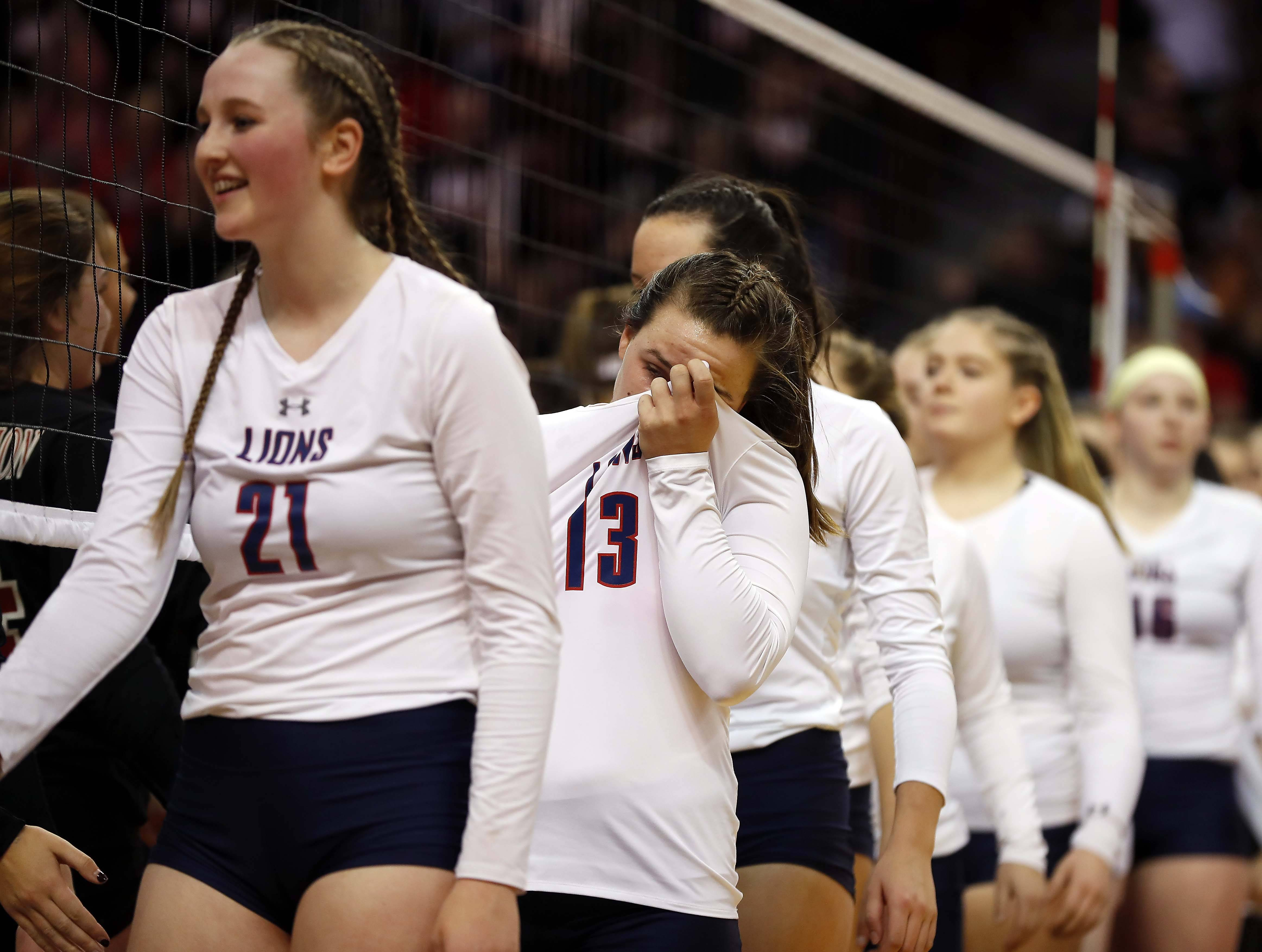 Saint Viator's Michaela Mueller (C) (13) and her teammates react after their loss in the semifinals of the IHSA Class 3A state girls volleyball tournament at Redbird Arena in Normal.