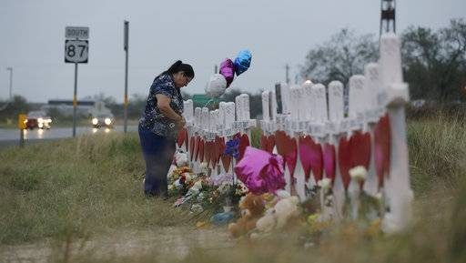 A woman visits a makeshift memorial along the highway for the victims of the church shooting at Sutherland Springs Baptist Church, Friday, Nov. 10, 2017, in Sutherland Springs, Texas. A man opened fire inside the church in the small South Texas community on Sunday, killing more than two dozen.