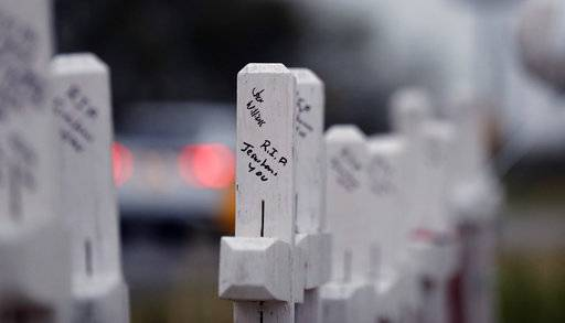Hand-written messages on crosses are part of a makeshift memorial for the victims of the church shooting at Sutherland Springs Baptist Church placed along the highway , Friday, Nov. 10, 2017, in Sutherland Springs, Texas. A man opened fire inside the church in the small South Texas community on Sunday, killing more than two dozen.