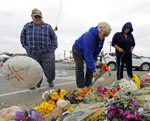Barbara Solano, center, places flowers at a makeshift memorial for the victims of the First Baptist Church shooting Thursday, Nov. 9, 2017, in Sutherland Springs, Texas. A man opened fire inside the church in the small South Texas community on Sunday, killing more than two dozen and injuring others.