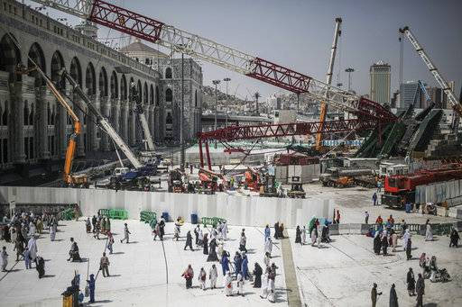 FILE - In this Sept. 15, 2015 file photo, Muslim pilgrims walk past the site of a crane collapse that killed over a hundred at the Grand Mosque in the holy city of Mecca, Saudi Arabia. A decades-old alliance between the ruling Al Saud and the Binladin family secured the latter's near-monopoly on major expansion work in Mecca and Medina. The reported arrest on Saturday, Nov. 4, 2017 of Bakr Binladin, who was Osama bin Laden's half brother and chairman of the expansive Saudi Binladin Group, signals the end of the Al Saud-Binladin family alliance.