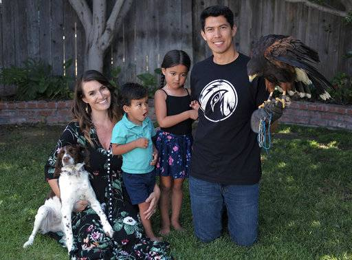 "In this June 30, 2017 photo falconer's Mike Bordonaro and his wife Alyssa pose for a photo with their children Hunter and Ayla in the families backyard in Oxnard, Calif. Known as ""The Hawk Pros."" husband-and-wife falconers Alyssa and Mike Bordonaro and their birds of prey are hired guns, brought in to scare away seagulls, pigeons and other ""pest birds"" that create nuisances and leave behind messes. The Bordonaros have about a dozen clients, from a recycling center in the agricultural city of Oxnard to the Los Angeles County Museum of Art and downtown Los Angeles' U.S. Bank Tower."
