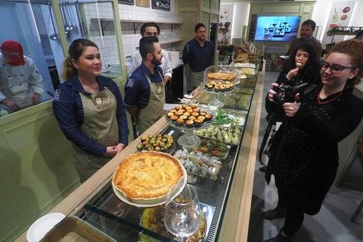In this photo taken on Thursday, Nov. 9, 2017, visitors taste cakes at the 'FICO Eataly World', 'La Fabbrica Italiana Contadina' ('The Italian Farmer Factory') agri-food park in Bologna, Italy. The man behind the Eataly Italian food empire wants to do for the high-end of Italian food what Milan Fashion Week has done for Italy's ready-to-wear industry: Create a global showcase for excellence that stimulates demand across the sector.  (Giorgio Benvenuti/ANSA via AP)