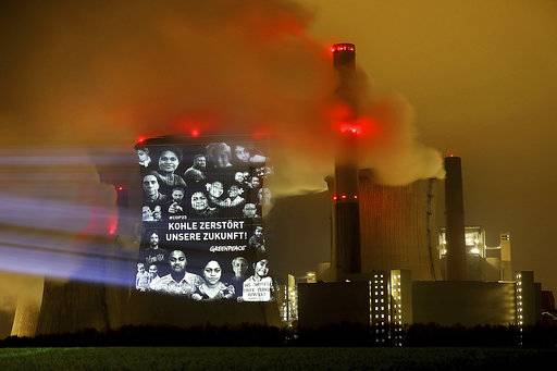 "Greenpeace activists project the writing ""Coal destroys our future"" on the cooling tower of the lignite power plant Neurath near Grevenbroich, western Germany, Friday morning, Nov. 10, 2017 during the global climate meeting in nearby Bonn. (Oliver Berg/dpa via AP)"