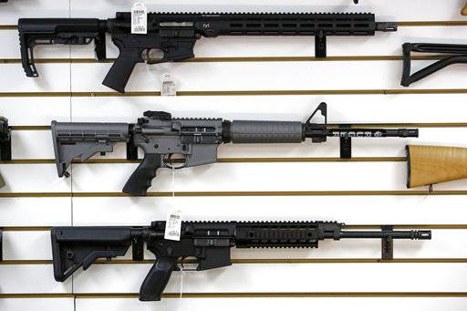 A Ruger AR-15 semi-automatic rifle, center, the same model, though in gray rather than black, used by the shooter in a Texas church massacre two days earlier, sits on display with other rifles on a wall in a gun shop Tuesday, Nov. 7, 2017, in Lynnwood, Wash. Gun-rights supporters have seized on the Texas church massacre as proof of the well-worn saying that the best answer to a bad guy with a gun is a good guy with a gun. Gun-control advocates, meanwhile, say the tragedy shows once more that it is too easy to get a weapon in the U.S.