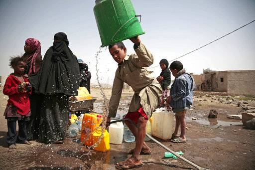 "FILE - In this July 12, 2017 file photo, a boy rinses a bucket as he and others collect water from a well that is allegedly contaminated with cholera bacteria, on the outskirts of Sanaa, Yemen. The United Nations and more than 20 aid groups said Thursday, Nov. 9, 2017, that the Saudi-led coalition's tightening of a blockade on war-torn Yemen could bring millions of people closer to ""starvation and death."" About two-thirds of Yemen's population relies on imported supplies, said the groups, which include CARE, Save the Children and Islamic Relief."