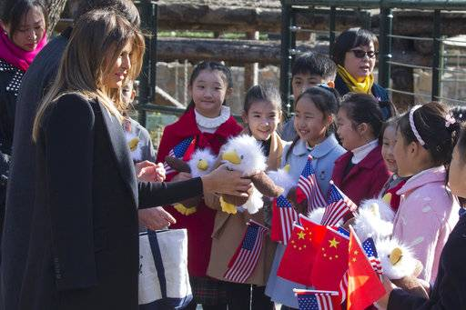 U.S. first lady Melania Trump hands out bald eagle dolls to Chinese children holding U.S. and Chinese flags near the Panda enclosure at the zoo in Beijing Friday, Nov. 10, 2017.