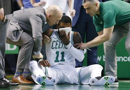 Team personnel assist Boston Celtics' Kyrie Irving (11) after he was injured during the first quarter of an NBA basketball game against the Charlotte Hornets in Boston, Friday, Nov. 10, 2017. Irving took an elbow to the face and left the game. (AP Photo/Michael Dwyer)