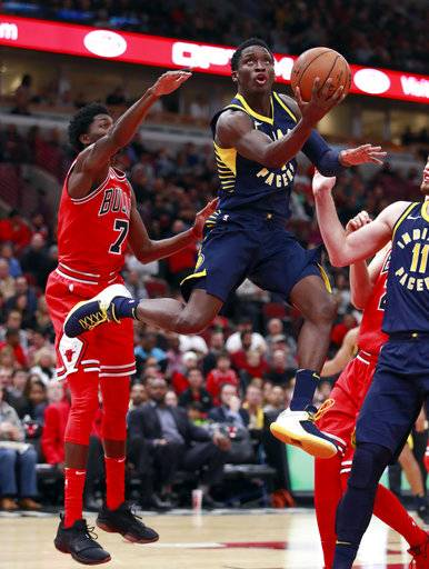 Indiana Pacers guard Victor Oladipo goes in for a lay-up past Chicago Bulls guard Justin Holiday (7) during the first half of an NBA basketball game in Chicago, on Friday Nov. 10, 2017. (AP Photo/Jeff Haynes)