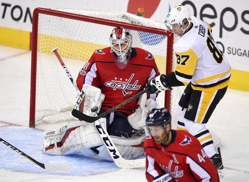 Pittsburgh Penguins center Sidney Crosby (87) battles for the puck against Washington Capitals goalie Braden Holtby (70) during the third period of an NHL hockey game, Friday, Nov. 10, 2017, in Washington. Capitals defenseman Brooks Orpik (44) looks on.