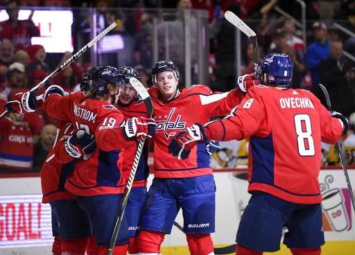 Washington Capitals defenseman John Carlson, second from right, celebrates his goal with left wing Alex Ovechkin (8), of Russia, center Nicklas Backstrom (19), of Sweden, and others during the first period of an NHL hockey game against the Pittsburgh Penguins, Friday, Nov. 10, 2017, in Washington.
