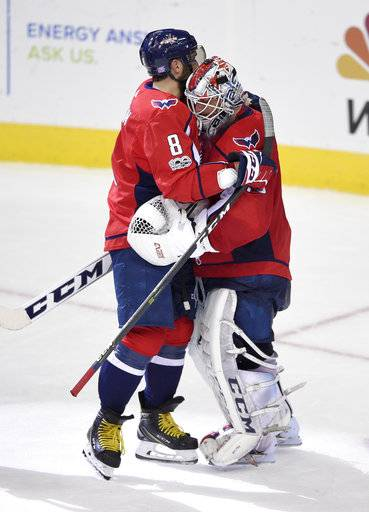 Washington Capitals left wing Alex Ovechkin (8), of Russia, hugs goalie Braden Holtby (70) after an NHL hockey game against the Pittsburgh Penguins, Friday, Nov. 10, 2017, in Washington.