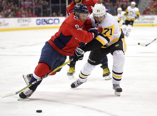 Washington Capitals defenseman Dmitry Orlov (9) and Pittsburgh Penguins center Evgeni Malkin (71), both of Russia, battle for the puck during the second period of an NHL hockey game, Friday, Nov. 10, 2017, in Washington.