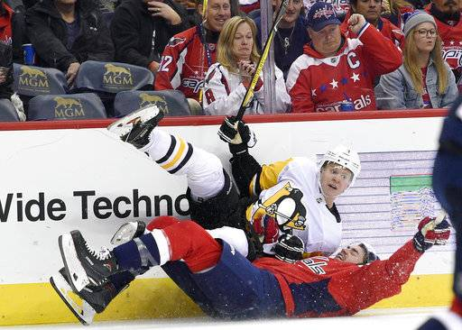 Pittsburgh Penguins defenseman Olli Maatta, top, of Finland, and Washington Capitals right wing Tom Wilson, bottom, slide on the ice during the second period of an NHL hockey game, Friday, Nov. 10, 2017, in Washington.