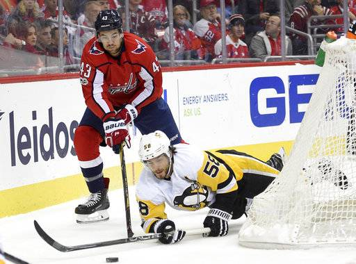 Washington Capitals right wing Tom Wilson (43) battles for the puck against Pittsburgh Penguins defenseman Kris Letang (58) during the first period of an NHL hockey game, Friday, Nov. 10, 2017, in Washington.