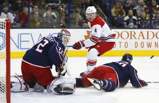 Columbus Blue Jackets' Sergei Bobrovsky, left, of Russia, makes a save as teammate David Savard, right, falls to the ice and Carolina Hurricanes' Haydn Fleury looks for the rebound during the first period of an NHL hockey game Friday, Nov. 10, 2017, in Columbus, Ohio.