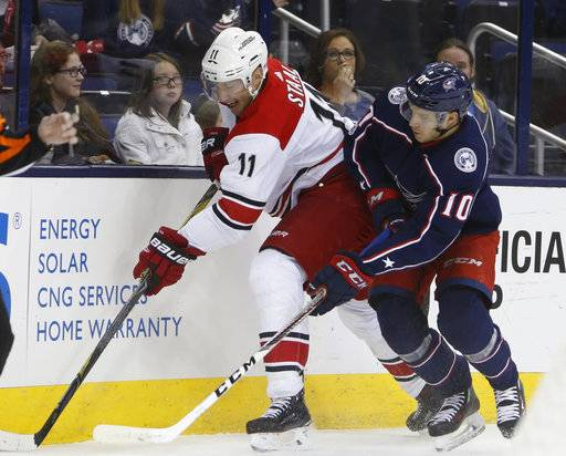 Carolina Hurricanes' Jordan Staal, left, and Columbus Blue Jackets' Alexander Wennberg, of Sweden, reach for the puck during the first period of an NHL hockey game Friday, Nov. 10, 2017, in Columbus, Ohio.