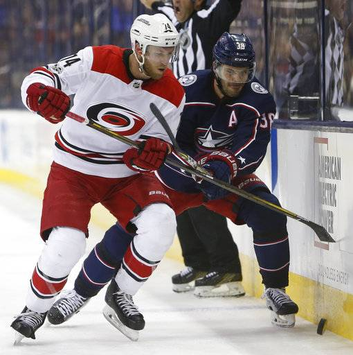 Carolina Hurricanes' Jaccob Slavin, left, and Columbus Blue Jackets' Boone Jenner scrap for a loose puck during the second period of an NHL hockey game Friday, Nov. 10, 2017, in Columbus, Ohio.