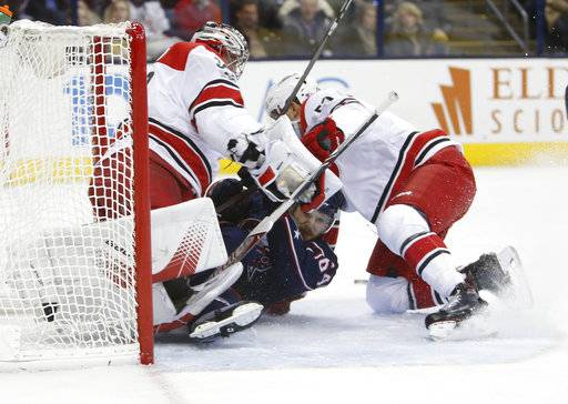 Carolina Hurricanes' Trevor van Riemsdyk, right, holds Columbus Blue Jackets' Tyler Motte as they collide with goaltender Cam Ward during the second period of an NHL hockey game Friday, Nov. 10, 2017, in Columbus, Ohio. van Riemsdyk was penalized on the play.