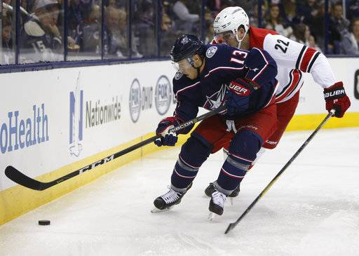 Columbus Blue Jackets' Cam Atkinson, left, carries the puck behind the net as Carolina Hurricanes' Brett Pesce defends during the second period of an NHL hockey game Friday, Nov. 10, 2017, in Columbus, Ohio.