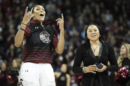 CORRECTS TO RECEIVING SEC CHAMPIONSHIP RING- South Carolina forward A'ja Wilson, left, and head coach Dawn Staley celebrate after receiving their SEC championship rings before an NCAA college basketball game Friday, Nov. 10, 2017, in Columbia, S.C. (AP Photo/Sean Rayford)