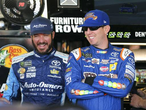Kyle Busch, right, and Martin Truex Jr. laugh inside the garage area before practice for the NASCAR Cup Series auto race at Phoenix International Raceway, Friday, Nov. 10, 2017, in Avondale, Ariz. Both drivers have secured a spot in the Championship 4 heading into Sunday's race.