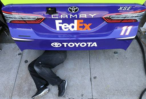 A member of driver Denny Hamlin's pit crew works under his race car before practice for the NASCAR Cup Series auto race at Phoenix International Raceway, Friday, Nov. 10, 2017, in Avondale, Ariz. Hamlin is one of five drivers looking to fill the final spot in the Championship 4.