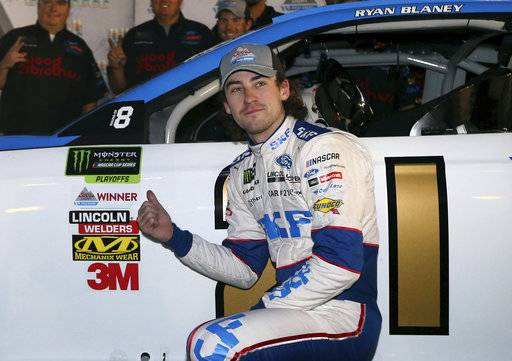 Ryan Blaney points to the pole award stuck on his car after winning the starting position for a NASCAR Cup Series auto race at Phoenix International Raceway, Friday, Nov. 10, 2017, in Avondale, Ariz.