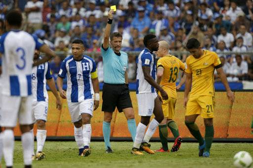 Italian referee Daniele Orsato awards a yellow card to Honduras' Johnny Palacios during the first leg of a soccer World Cup qualifier play-off at the Olympic Stadium in San Pedro Sula, Honduras, Friday, Nov. 10, 2017. (AP Photo/Moises Castillo)