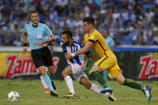 Australia's Tomi Juric, right, fights for the ball with Honduras' Alfredo Mejia, center, as referee Daniele Orsato, from Italy, looks on, during the first leg of a soccer World Cup qualifier play-off at the Olympic Stadium in San Pedro Sula, Honduras, Friday, Nov. 10, 2017.