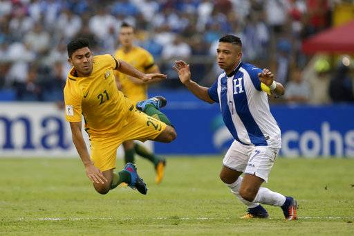 Australia's Massimo Luongo, left, is taken down by Honduras' Emilio Izaguirre during the first leg of a soccer World Cup qualifier play-off at the Olympic Stadium in San Pedro Sula, Honduras, Friday, Nov. 10, 2017.